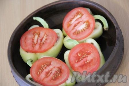 На дно жаропрочной формы налить немного воды. Выложить перцы с фаршем. Помидор вымыть и нарезать кружочками. На каждый перчик, поверх фарша, выложить кусочек помидора.
