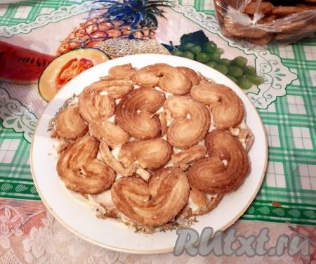 Берем блюдо, слегка смазываем кремом область будущего торта и выкладываем печенье, макая их в крем. Дырочки между печеньем заполняем поломанным печеньем и сверху промазываем кремом.