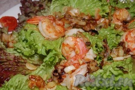 Выложить обжаренные креветки с луком пореем на листья салата.