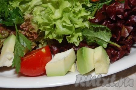 Разложить помидоры и авокадо по краю тарелки.