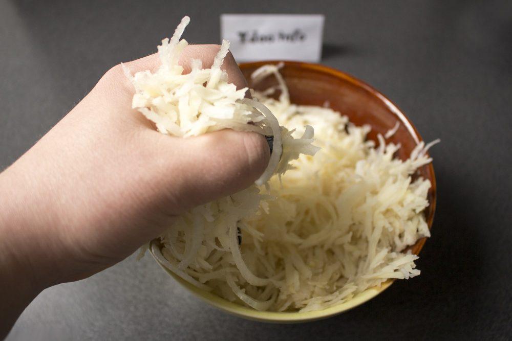натертый на крупной терке картофель отжимают руками от лишней влаги