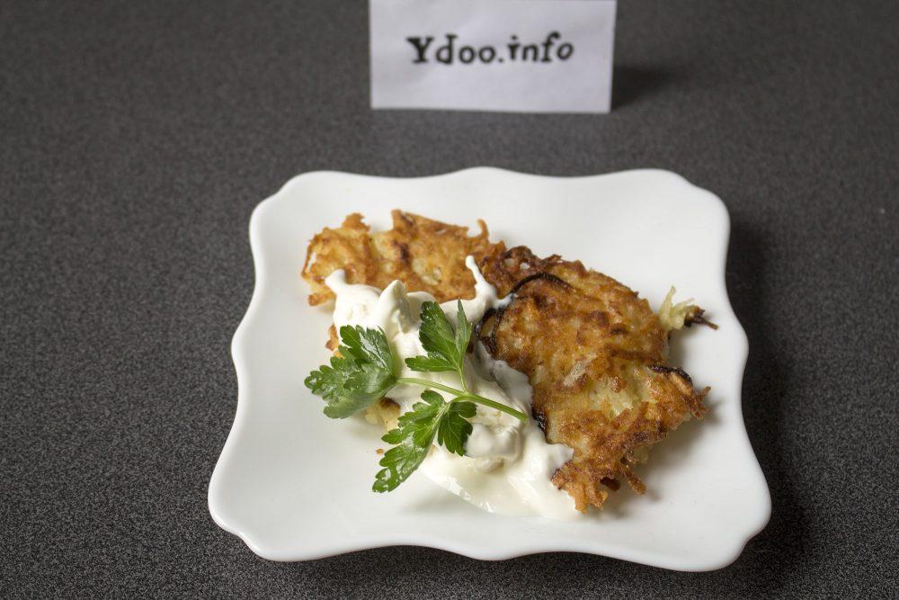 латкесы со сметаной в белом блюдце на столе