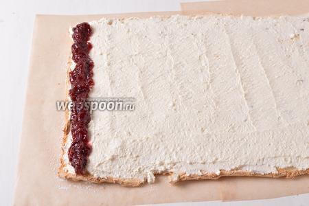 Смазать корж творожным кремом. Вдоль короткого края коржа выложить полоску из вишнёвого джема (70 грамм).