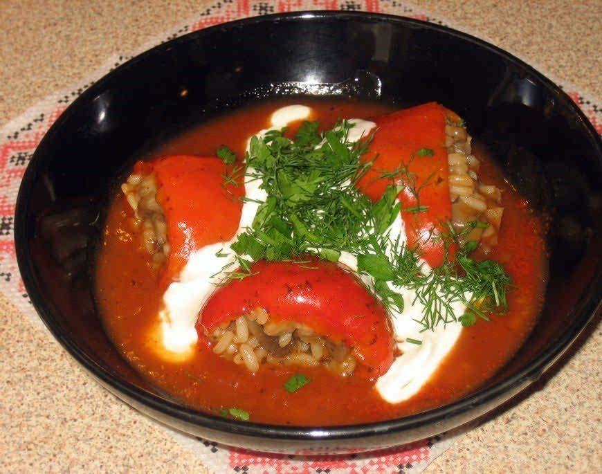 Фаршированный перец в тарелке со сметаной