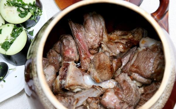 Обжаренные кусочки мяса в керамическом горшке на столе
