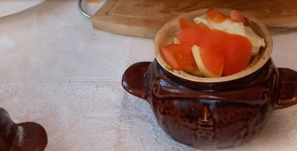 Керамический горшочек с кусочками помидора и репчатого лука на столе