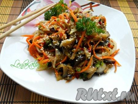 Накрыть посуду с закуской крышкой и поставить в холодильник на 2-3 часа. Выложить баклажаны с морковью по-корейски горкой, украсить зеленью, измельченным острым перцем чили и зернами кунжута.