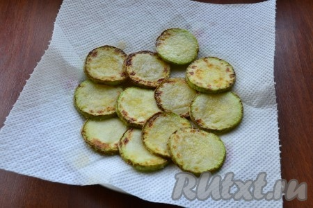 Обжарить кабачки на растительном масле до румяности с двух сторон, после чего выложить их на бумажное полотенце для удаления лишнего жира.