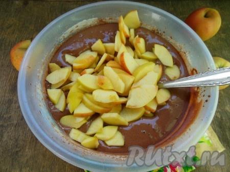Выложите кусочки нарезанных яблок в шоколадное тесто и перемешайте.