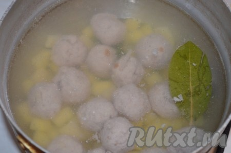 В кипящую воду положить лавровый лист, картошку и фрикадельки, посолить. Варить 7 минут после закипания воды.
